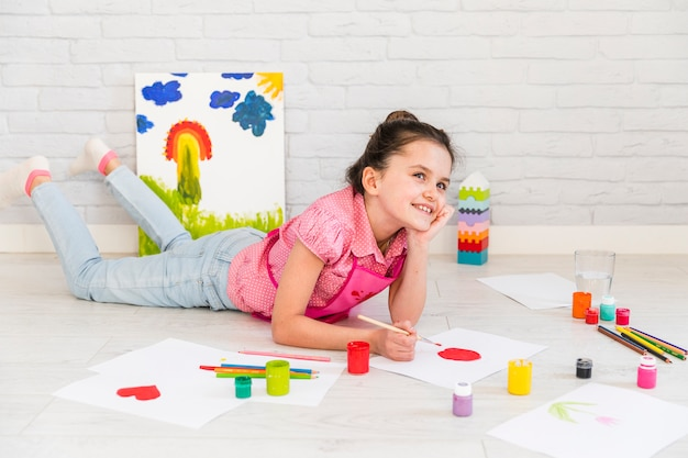 Smiling girl lying on floor painting on white paper with red brush