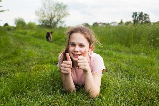 Smiling girl lying on green grass and showing thumb up gesture in park