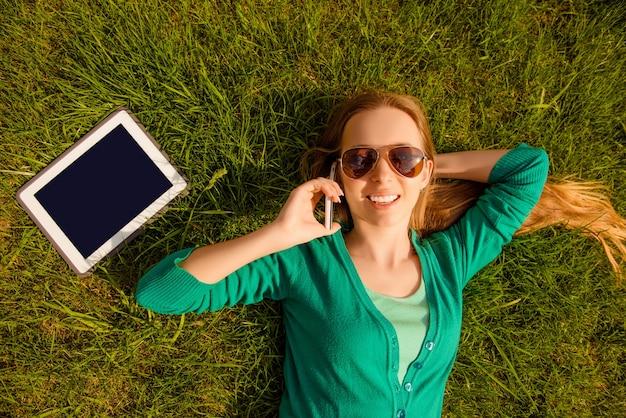 Улыбающаяся девушка лежит на лужайке с планшетом и разговаривает по телефону