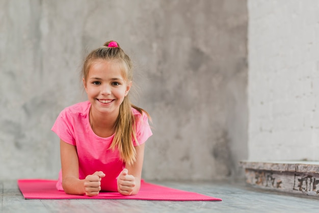 Smiling girl lying on pink exercise mat against concrete backdrop