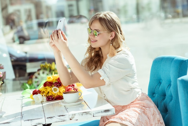 Smiling girl makes a selfie sitting on the terrace of cafe