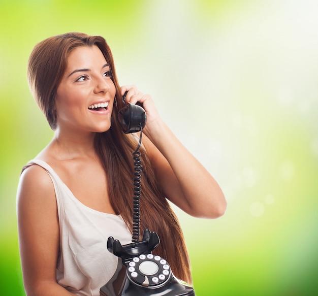 Улыбается девушка делает вызов по стационарный телефон