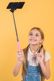 Smiling girl making gesture taking selfie from mobile stick against yellow backdrop