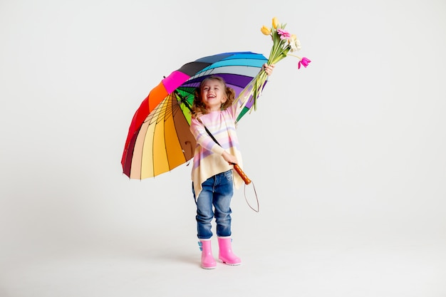Smiling girl in matching pink shirt and rain boots holding rainbow umbrella on white background