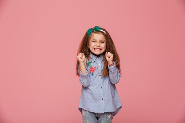 Smiling girl model in hair hoop and fashion clothes expressing happiness gesturing with clenched fists