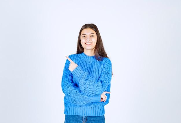 Улыбающаяся девушка модель указывая вверх и с нетерпением жду серо-белого цвета.