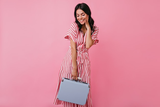 Smiling girl modestly looks down, posing with mini suitcase. full-length photo of lady with curly long hair in stylish outfit.