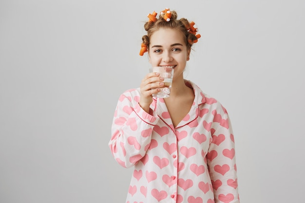 Smiling girl in nightwear drinking water, using hair curlers