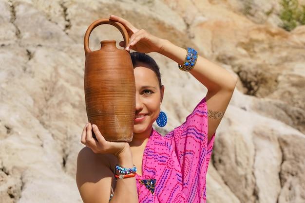 Улыбающаяся девушка восточной внешности в этническом платье с глиняным кувшином на фоне размытого пустынного пейзажа