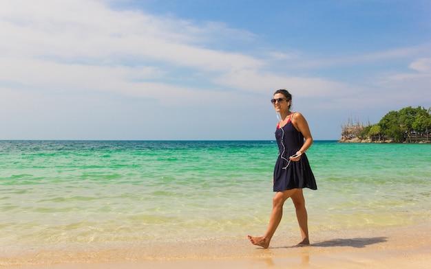Улыбающаяся девушка в синем платье слушает музыку во время прогулки по берегу и держит мобильный телефон, подключенный к наушникам, на острове ко пханган, таиланд