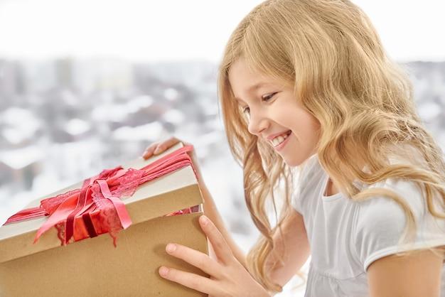 赤い弓でボックスを開く笑顔の女の子。