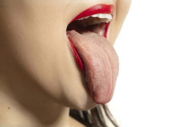Улыбающаяся девушка открывает рот и показывает длинный большой гигантский язык, изолированный на белой стене. выглядит потрясенным, привлеченным, удивленным и удивленным. copyspace для рекламы. человеческие эмоции, маркетинг.