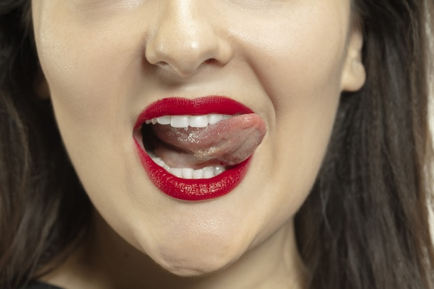 Улыбающаяся девушка открывает рот и показывает длинный большой гигантский язык на белом.