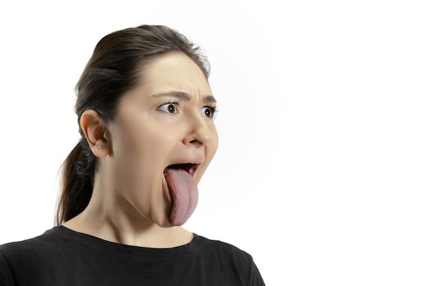 Ragazza sorridente che apre la bocca e mostra la lunga lingua gigante isolata sul muro bianco. sembra scioccato, attratto, meravigliato e stupito. copyspace per l'annuncio. emozioni umane, marketing.