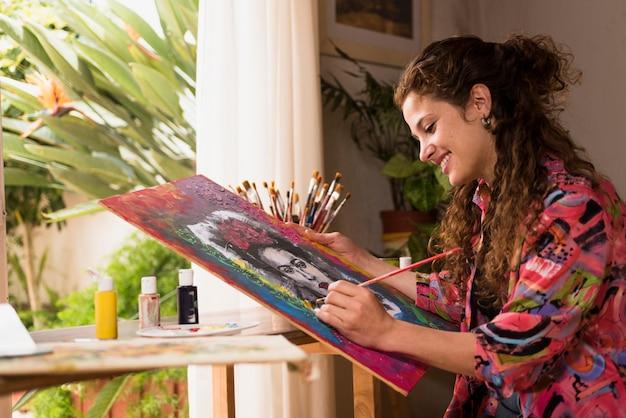 Улыбающаяся девушка рисует холст