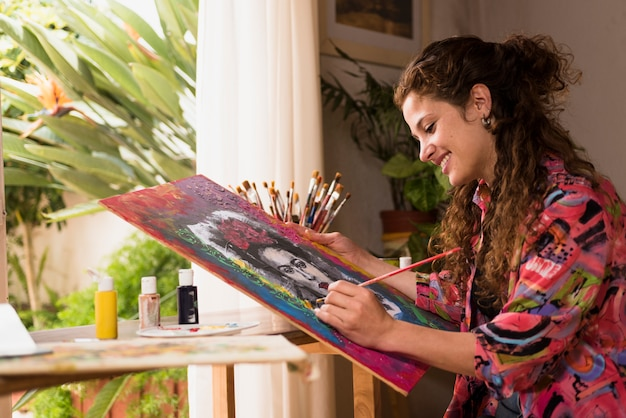 Smiling girl painting a canvas