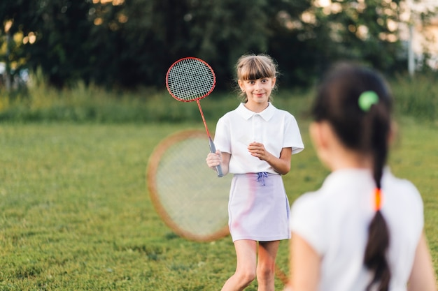 Smiling girl playing badminton with her friend