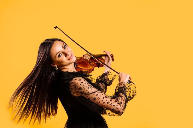 Улыбающаяся девушка играет на скрипке