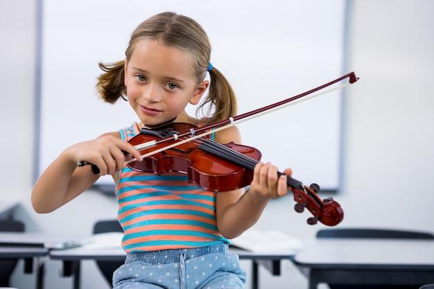 教室でバイオリンを弾いて笑顔の女の子