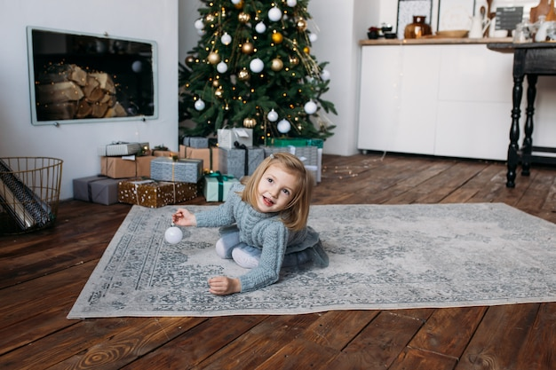 Smiling girl playing with christmas decoration