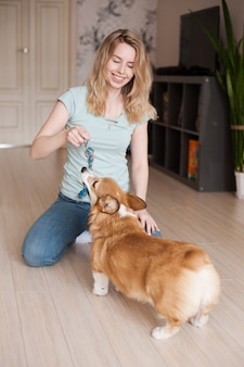 Smiling girl playing with her welsh corgi pembroke puppy, happy cute dog