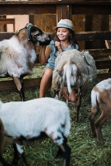 Smiling girl playing with sheep in the barn