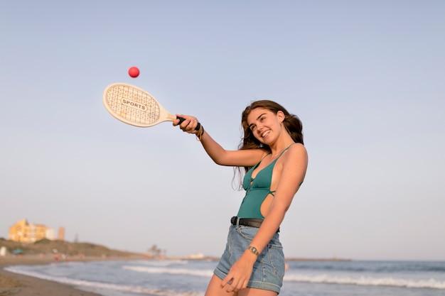 Ragazza sorridente che gioca con la pallina da tennis e la racchetta alla spiaggia