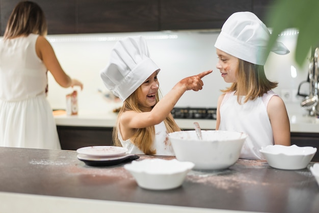 Smiling girl pointing her sister with messy hands in kitchen