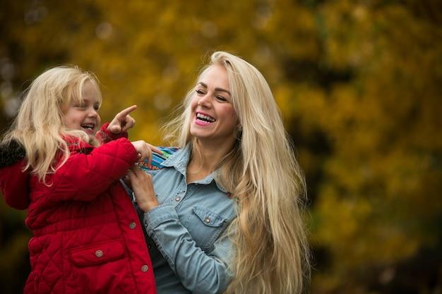 Ragazza sorridente che punta a qualcosa a sua madre