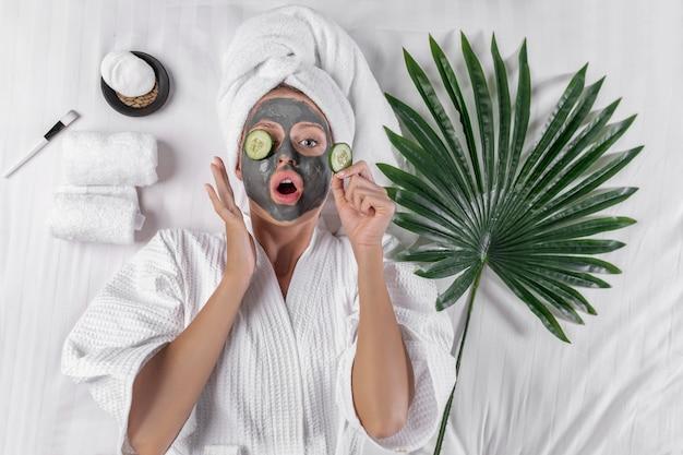 Улыбающаяся девушка позирует с глиняной маской на лице