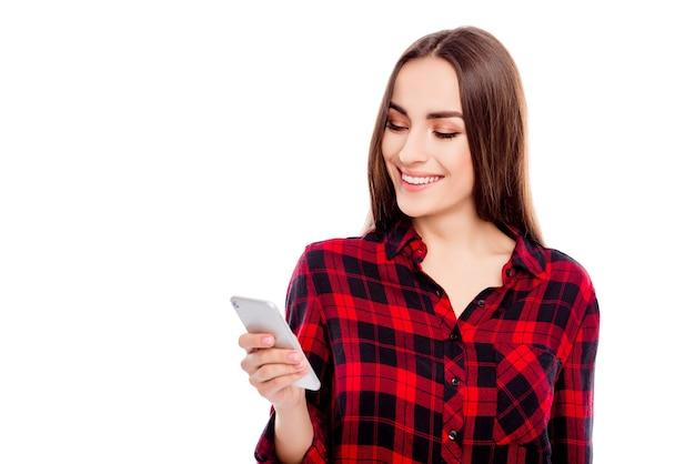 Улыбающаяся девушка, читающая сообщение на мобильном телефоне на белом пространстве