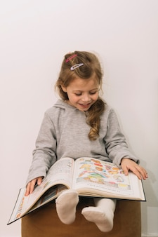 Smiling girl reading on pouf