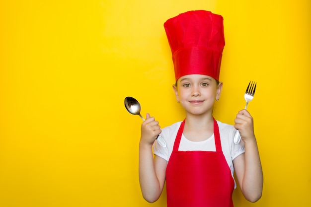 Smiling girl in a red chef's suit holding a spoon and fork, inviting to dinner on yellow