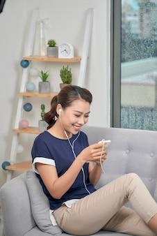 自宅でリラックスし、イヤホンで音楽を聴いている笑顔の女の子。ソファに電話を持っている嬉しい若い女性の屋内写真。