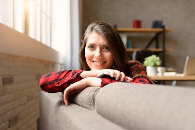 彼女のスマートフォンでソファでリラックスして笑顔の女の子