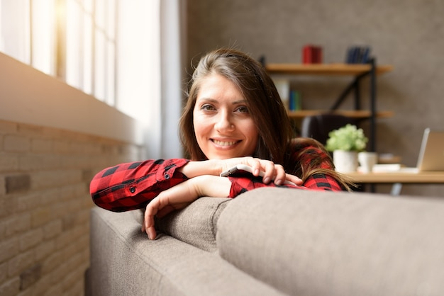 Smiling girl relaxing on a sofa with her smartphone