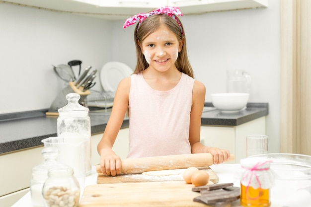Smiling girl rolling dough on messy kitchen