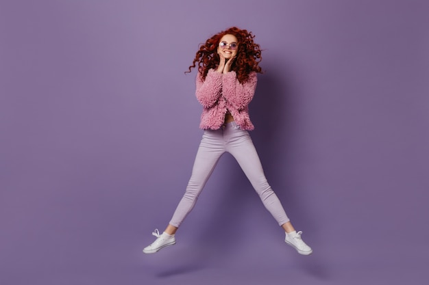 Smiling girl in round sunglasses jumps. woman with red curls in bright outfit is having fun on purple space.