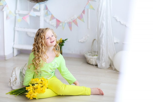 Smiling girl of school age with yellow flowers in her hands