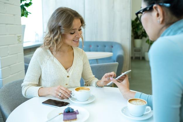 カフェのテーブルでデザートとカプチーノを持っている間、彼女の友人のスマートフォンでスクロールしている笑顔の女の子