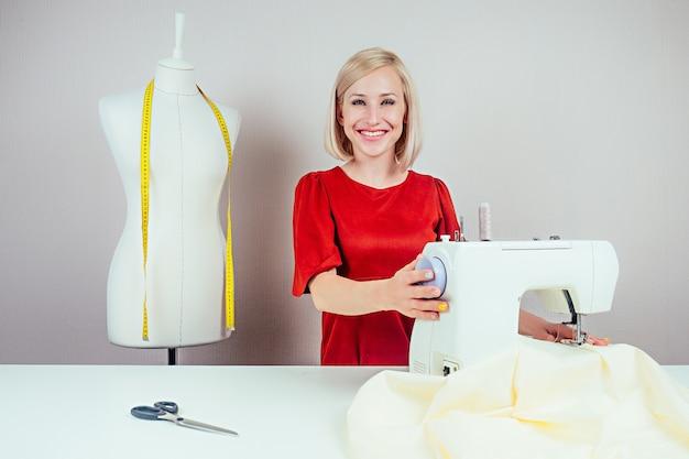 白い背景の上の黄色の巻尺でミシンとマネキンに取り組んでいる笑顔の女の子の針子。