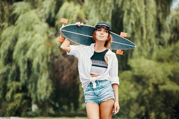 Smiling girl showing attitude close up portrait, holding longboard