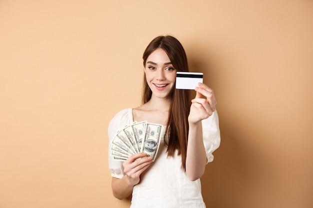 カメラにプラティッククレジットカードを見せて、胸の近くにドル札を持って、ベージュの背景の上に立っている笑顔の女の子。