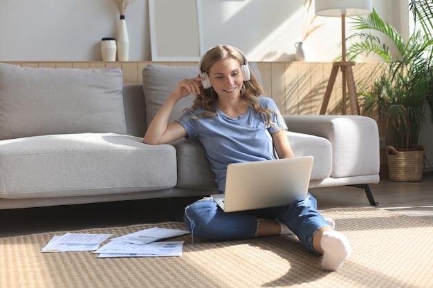 笑顔の女の子がノートパソコンでウェビナーを見ながらソファの近くに座っています。幸せな若い女性は、オンラインの遠いコースで勉強します。