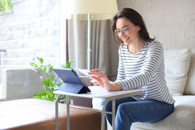 笑顔の女の子は、ラップトップでウェビナーを見ながらソファに座っています。幸せな若い女性は、オンラインの遠いコースで勉強します。