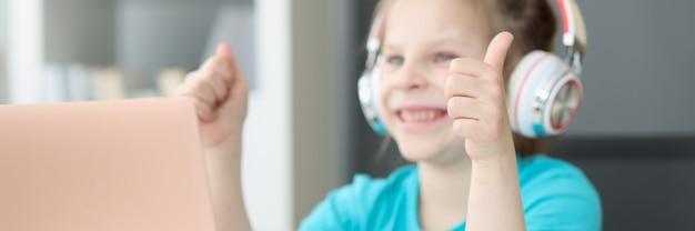 笑顔の女の子がヘッドフォンでラップトップに座って親指を表示します