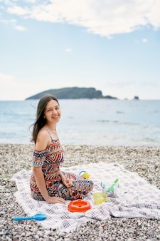 웃는 소녀는 아이들 장난감이 있는 자갈 해변의 침대보에 앉아 있다