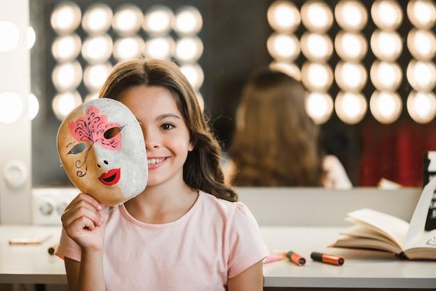 彼女の顔の前にマスクを持っている舞台裏に座っている笑顔の女の子