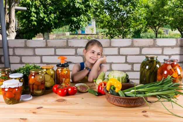 新鮮な野菜と漬物の瓶で覆われたテーブルに座っている笑顔の女の子は、庭の屋外で保存します