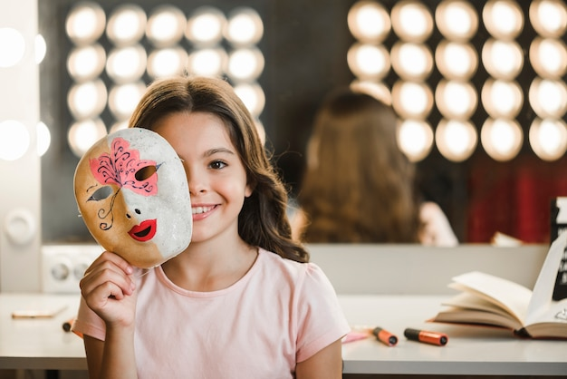 Smiling girl sitting at backstage holding mask in front of her face